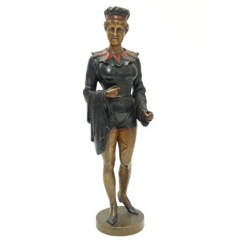 1300 - A 20thC carved wooden sculpture modelled as a woman wearing a jester style outfit with polychrome de...