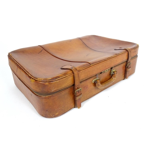1312 - A vintage leather suitcase with carry handle and zip and buckle fasteners. Approx. 16 1/2