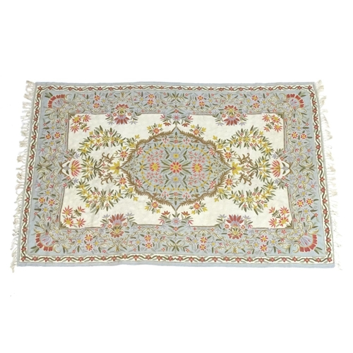 1319 - A 19thC hand embroidery / crewel work rug with floral and foliate decoration. Approx. 71