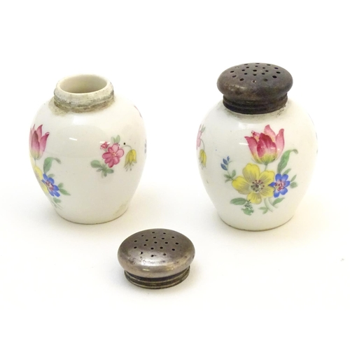 1328 - A German three piece ceramic cruet set with floral decoration, the white metal tops marked 835. Make...