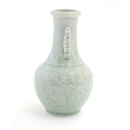 1 - A Chinese celadon green baluster vase with twin handles and stylised foliate design. Approx. 6 1/4