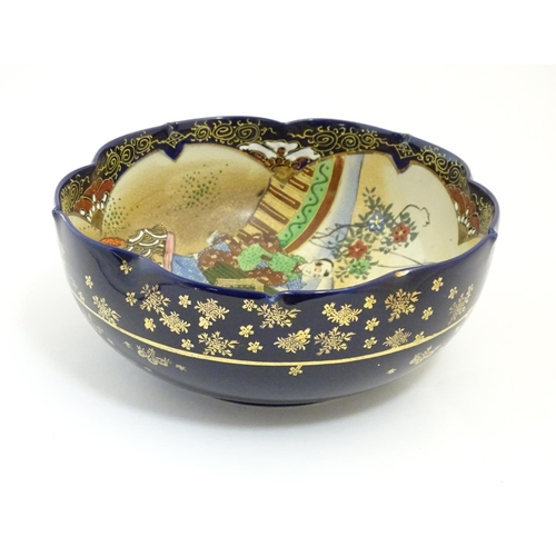 11 - A Japanese export bowl with a lobed rim, decorated with Geisha girls with fans and flowers in a land...