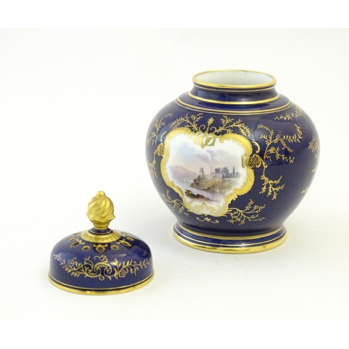 119 - A Coalport pot pourri with a cobalt blue ground with gilt detail and a central hand painted landscap...