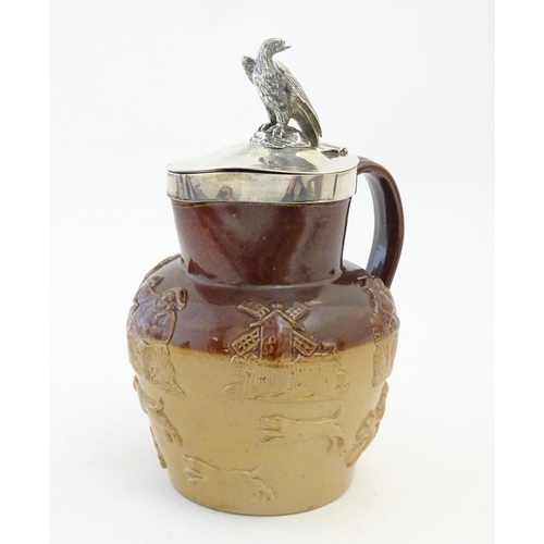 124 - A Victorian salt glaze two tone harvest jug with silver mounts and lid surmounted by an eagle, hallm...