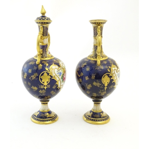 140 - Two Royal Doulton pedestal vases with cobalt blue ground, gilt highlights and hand painted floral an...