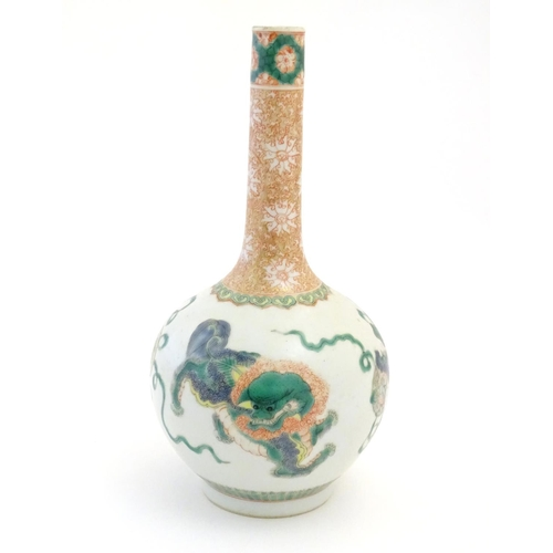19 - A Chinese bottle vase decorated with stylised foo dogs / dragons. The neck with floral and foliate d...