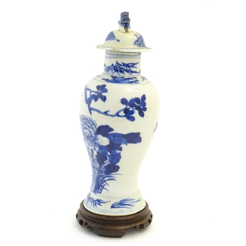 21 - A Chinese blue and white vase and cover with floral, foliate and bird detail. The lid with foo dog f...