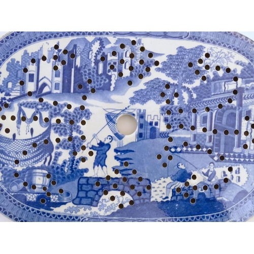 25 - An English blue and white strainer with chinoiserie decoration depicting a fishing village with figu...