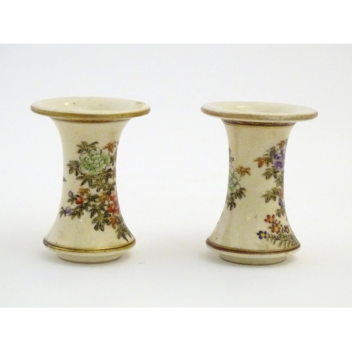 28 - A pair of Japanese miniature Satsuma vases with flared rims and bases, decorated with flowers and fo...