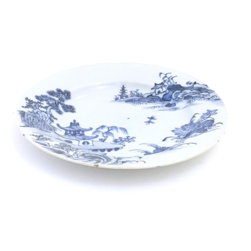 29 - A Chinese blue and white plate with a landscape scene with pagodas, flowers, etc. Approx. 9