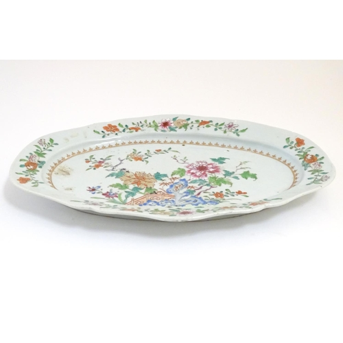 3 - A Chinese famille rose oval dish with hand painted floral and foliate detail, with peonies and bloss...