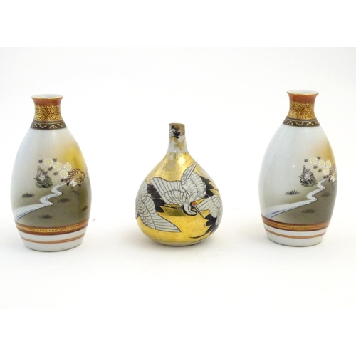 33 - Three Japanese vases, comprising a pair decorated with a landscape scene with quail birds and flower...