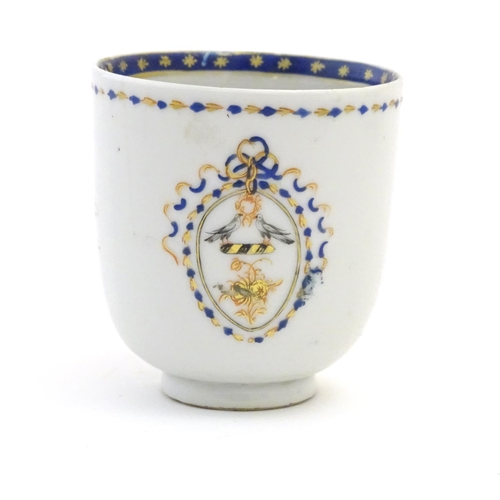 36 - A Chinese export tea cup with hand painted decoration depicting an armorial crest with birds, with a...