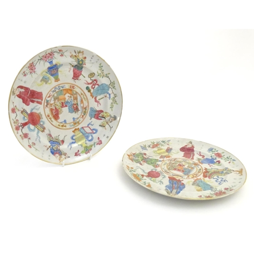 38 - A pair of Chinese famille rose plates decorated with warrior figures / heroes with auspicious symbol...