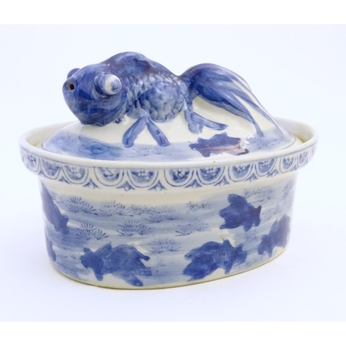 42 - A Chinese blue and white dish and cover of oval form, the lid surmounted by a fish in relief, the bo...