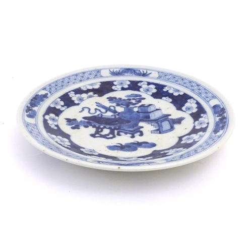 43 - A Chinese blue and white plate decorated with auspicious artifacts such as scrolls, vases and flower...