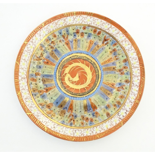 47 - An Oriental plate in the Kutani palette the centre with stylised dragon detail, with banded motif bo...
