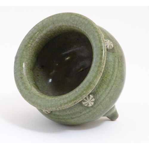5 - A Chinese three footed censor with a crackle glaze and floral roundels in relief. Approx. 3 1/4