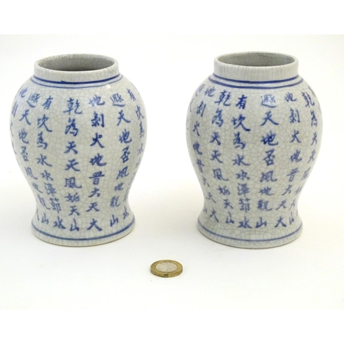52 - A pair of Chinese blue and white vases with script decoration. Approx. 5 1/2
