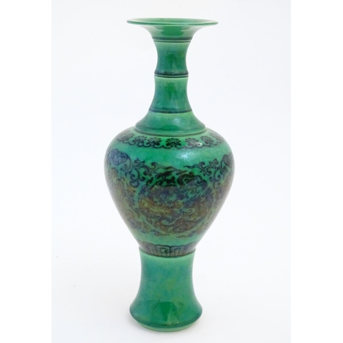 53 - A Chinese footed bulbous vase with a flared rim, the body decorated with scrolling dragon roundels a...