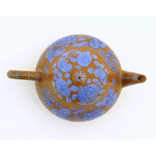 57 - A Chinese Yixing clay teapot with blue flower and butterfly decoration. Incised character marks unde...