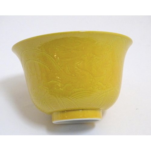 6 - A Chinese dragon bowl with a yellow ground with incised decoration depicting dragons and stylised cl...