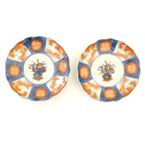 64 - Two Japanese plates in the Imari palette with scalloped edges, the centre decorated with flowers in ...