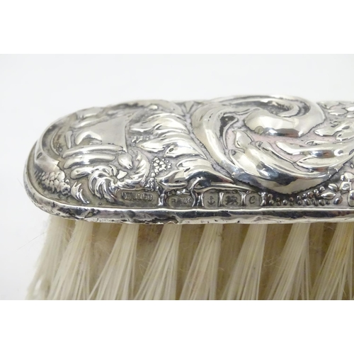 281 - A silver handled brush together with a silver backed brush  both with embossed decoration. Hallmarke...