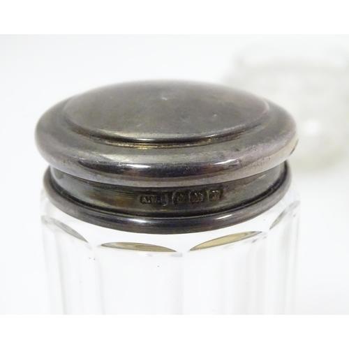 306 - Two silver lidded glass dressing table jars. Hallmarked Birmingham 1902 maker Adie & Lovekin Ltd and...