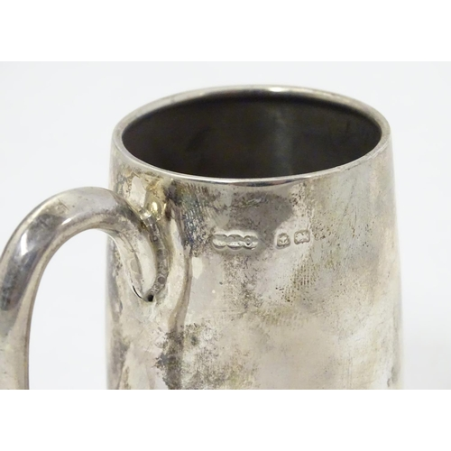 353 - A silver christening mug with loop handle. Hallmarked Birmingham 1918 maker Wilmot Manufacturing Co....