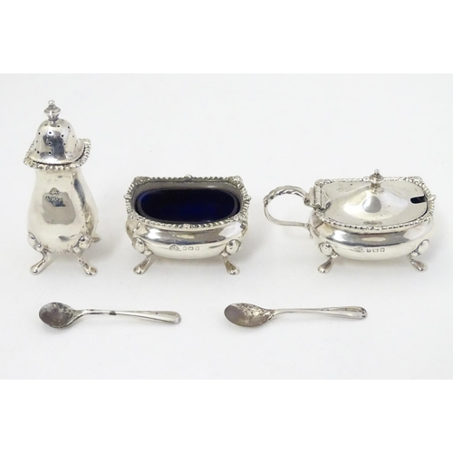 357 - A silver three piece cruet set comprising salt, mustard and pepper pot, with blue glass liners and m...