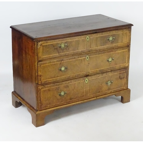 1373 - An 18thC walnut chest of drawers with a feather banded top above three long drawers with crossbanded...