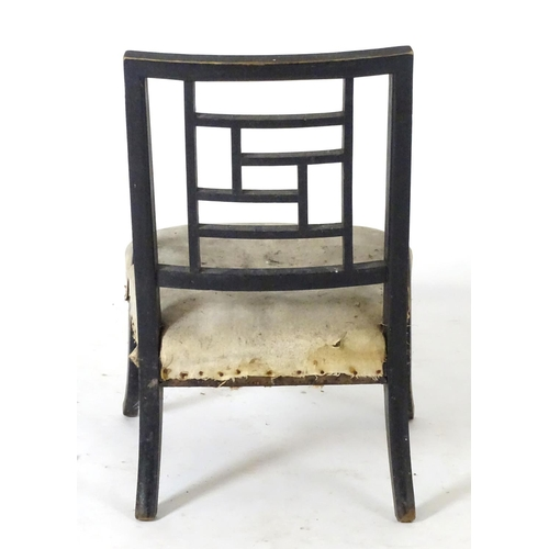 1386 - A late 19thC Aesthetic movement nursing chair in the manner of E.W Godwin with an ebonised finish an...