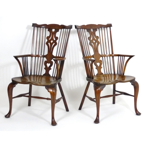 1411 - A pair of 20thC elm and yew Windsor armchairs, having comb backs and pierced central splats above sh...