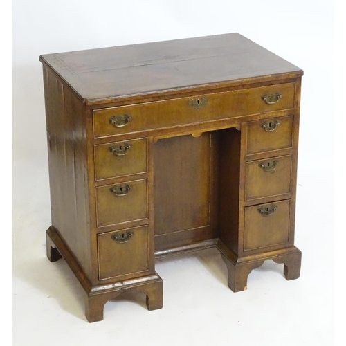 1412 - An early 20thC walnut desk with a quarter veneered and crossbanded top above one long drawer and six...