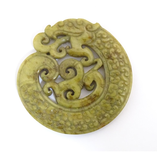 1005 - Three Oriental carved roundels, comprising two hardstone examples with stylised dragons, and one car...