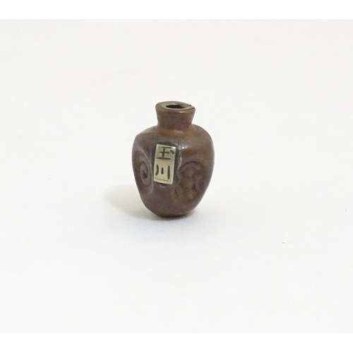 1014 - A Japanese ojime bead formed as a stylised vase with impressed detail and applied character mark tab...