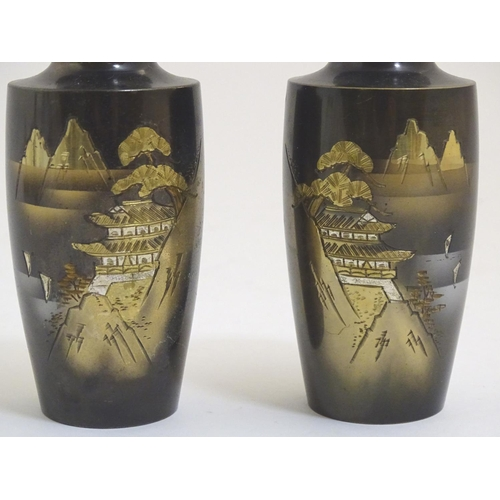 1031 - A pair of Oriental vases with chokin style engravings depicting a mountain landscape scene with a pa...