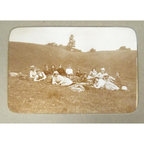 801 - An early 20thC photograph album with sepia and monochrome photos to include group shots in the count...