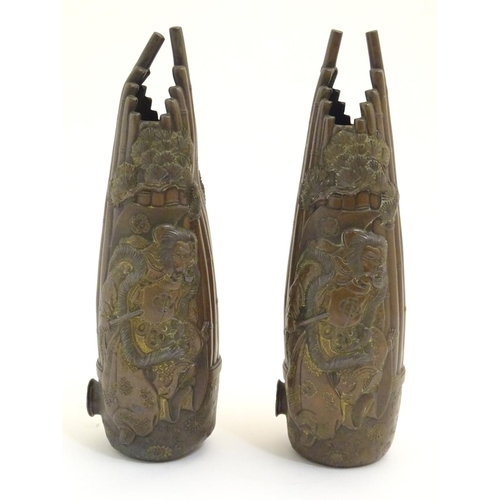 986 - A pair of Oriental cast vases depicting warriors duelling in relief with stylised bamboo and foliage...