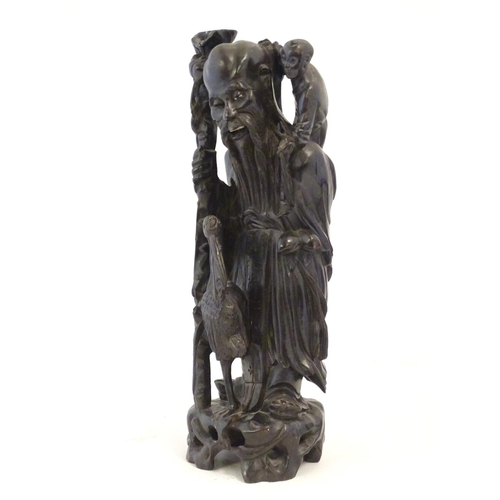 1278 - Three 20thC carved figures comprising an Oriental elder with a staff, child and crane; a Buddha figu...