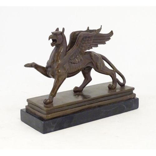 1299 - A 20thC cast model of a griffin with the body of a lion and the head and wings of an eagle. After Pi...