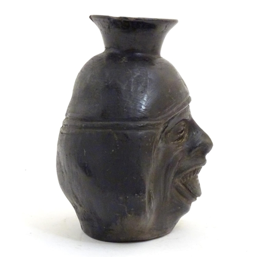 1093 - An unusual Inca blackware / Chimu style pottery vase modelled as a face. Approx. 6 1/2