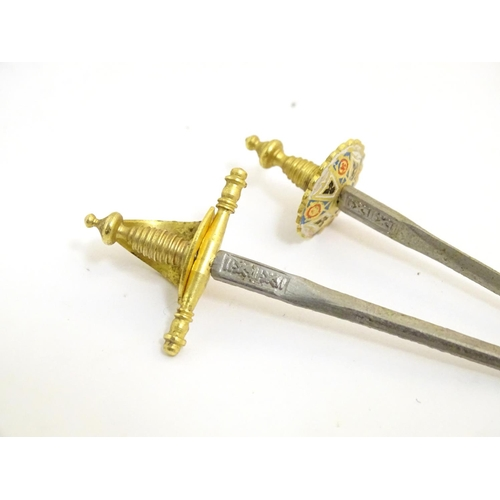 1113 - A 20thC set of four miniature Toledo swords in a gilt and enamel stand. Approx. 4 1/2