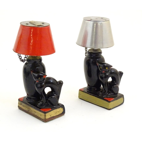1114 - A collection of novelty, table and pocket lighters, comprising a pair formed as table lamps upon boo...