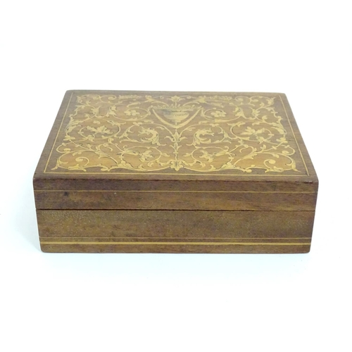 1200 - A late 19th / early 20thC Continental marquetry jewellery box with scrolling floral and foliate deta...