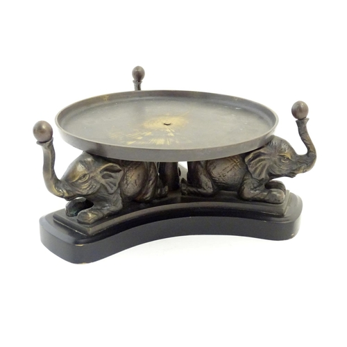 1216 - A 20thC circular stand with a triform base with cast elephant supports. Approx. 4 1/4