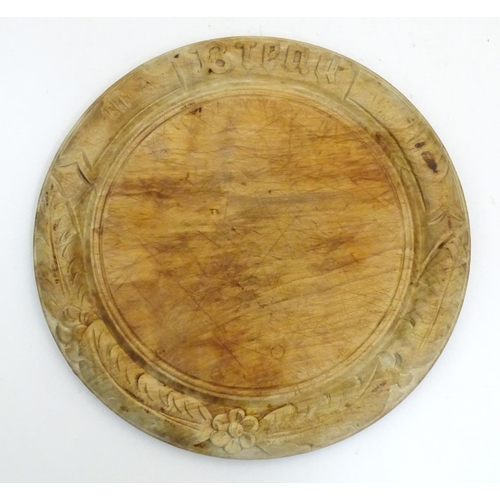 1160 - A Victorian carved sycamore bread board of circular form with flower and foliate detail. Approx. 11 ...