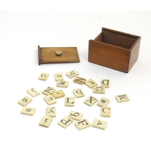 1165 - A 19thC box with a sliding lid containing 26 bone tiles each depicting a letter of the alphabet, upp...