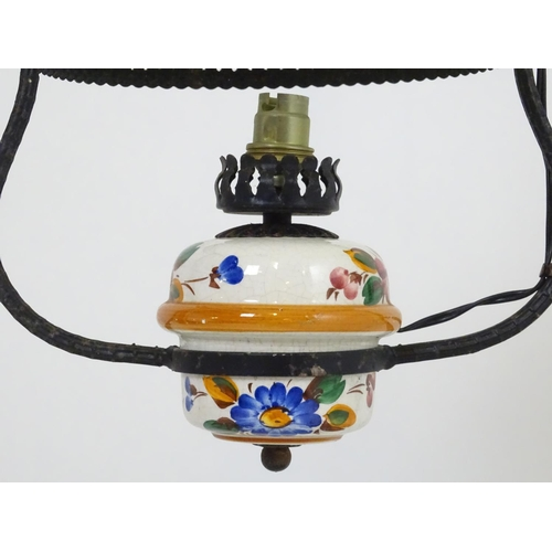 892 - A pendant hanging oil lamp with painted ceramic reservoir and white glass shade. Converted for elect...